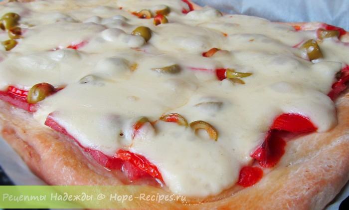 Аппетитная домашняя пицца с сыром, оливками, ветчиной и помидорами