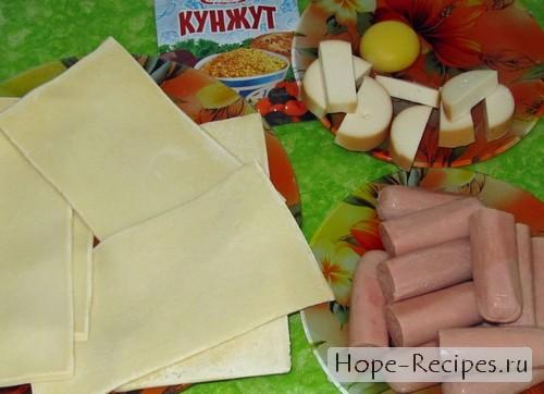 Слоеное тесто, сосиски, сыр, желток и кунжут