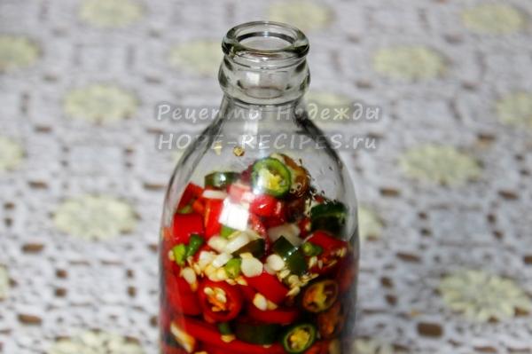 В стеклянную бутылку складываем нарезанный перец и чеснок, заливаем рыбным соусом